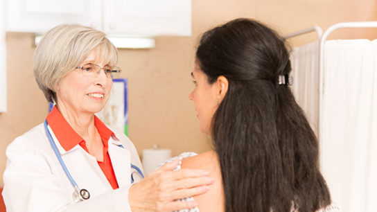 A patient receives a physical breast exam.