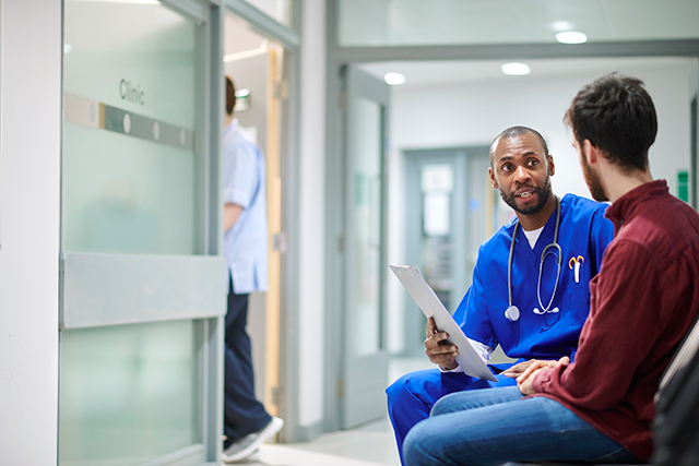 A male nurse obtains information from a clinic patient.