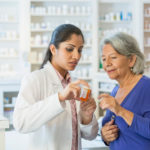 A pharmacist assists and older patient with cancer medication.