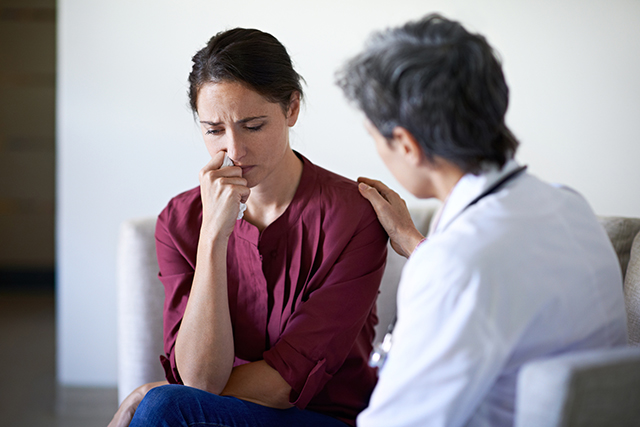 A nurse consoles a caregiver.