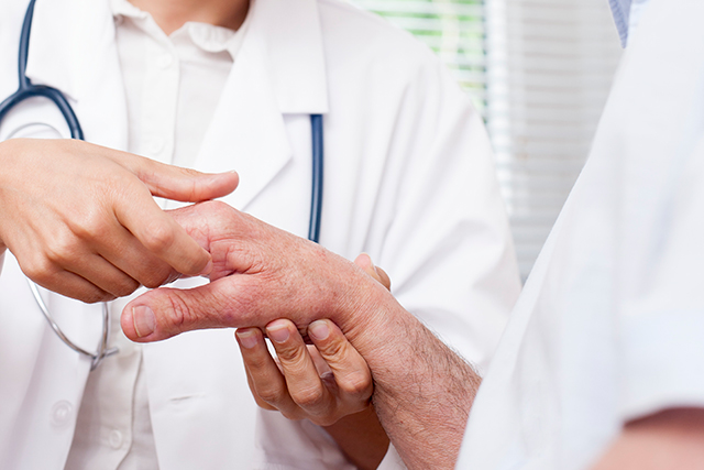 A clinician examines a patient with arthritis.