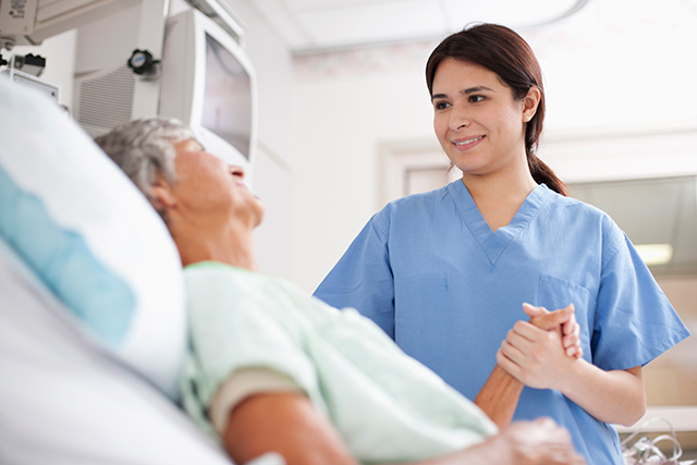 A nurse comforts a patient with advanced cancer.
