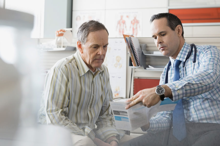 A clinician reviews prostate care information with his patient.