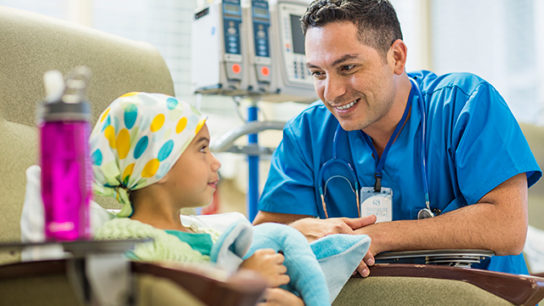 Conferring with a young patient receiving chemotherapy.