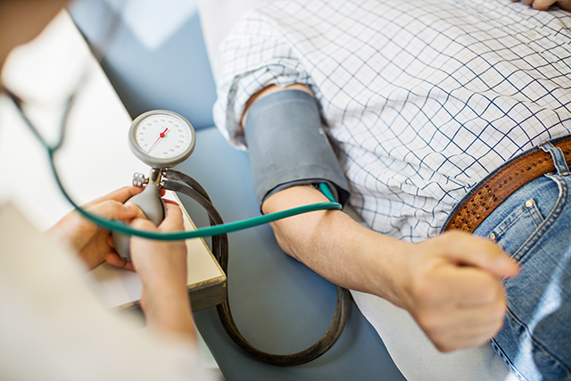 Conducting a routine blood pressure review.