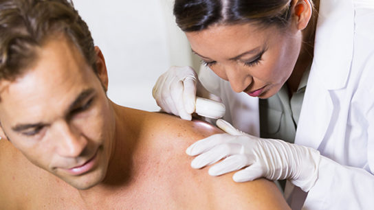 Dermatologist examines a patient's skin for signs of skin cancer.