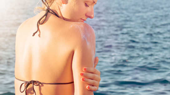 applying sunscreen to help prevent skin cancer.