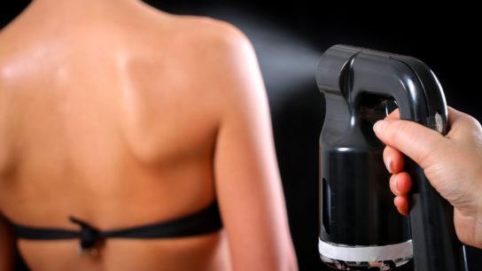 Applying a spray tan product.