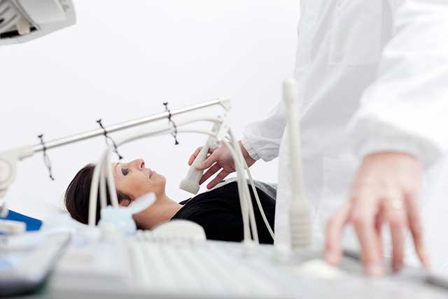 A patient undergoes thyroid screening.