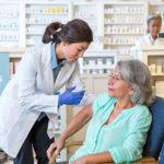 A pharmacist administers a flu shot.