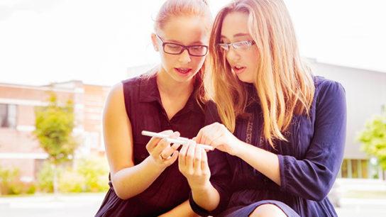 Adolescents examine e-cigarette devices.