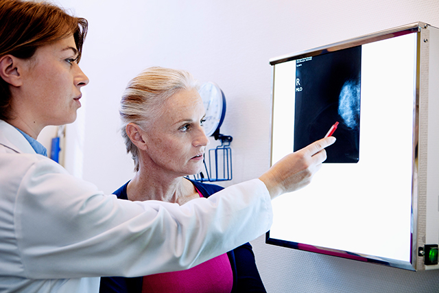 A patient and clinician review mammography results.
