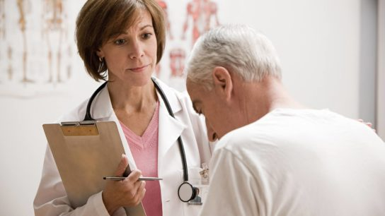 A female doctor examines an elderly male patient.