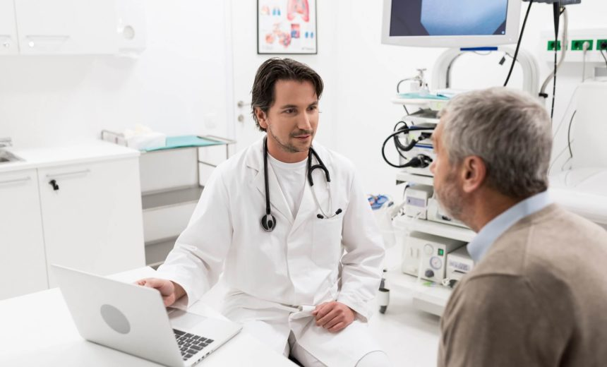 A doctor speaks with an old, white patient.