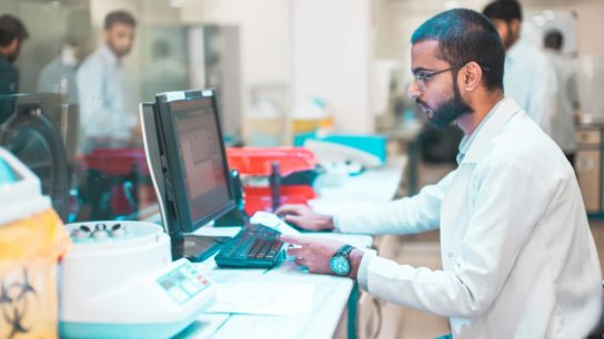 A paramedia works on a computer in a medical bay.