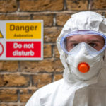 worker wearing protective clothing handles asbestos