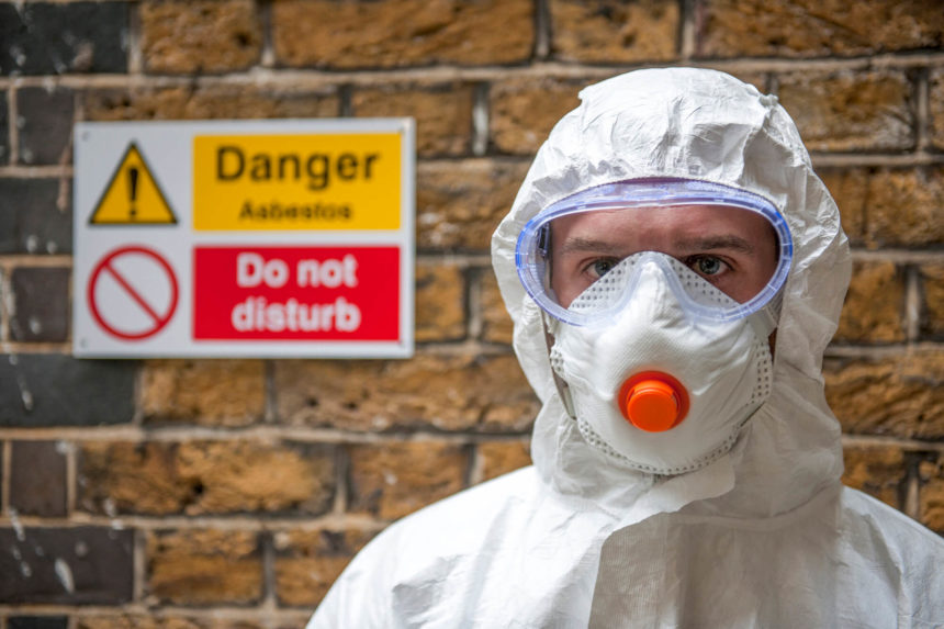 worker wearing protective clothing handles asbestos