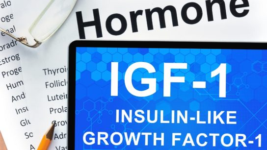 Papers with hormones list and tablet with words Insulin-like growth factor-1
