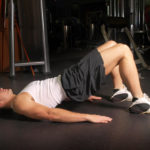 A man performs pelvic exercises.