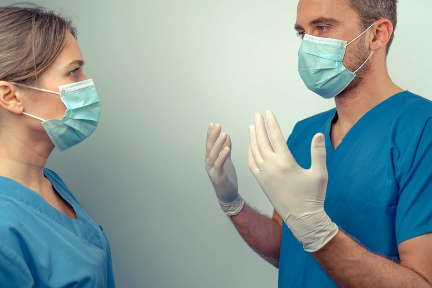 Masked medical workers discuss patient care.