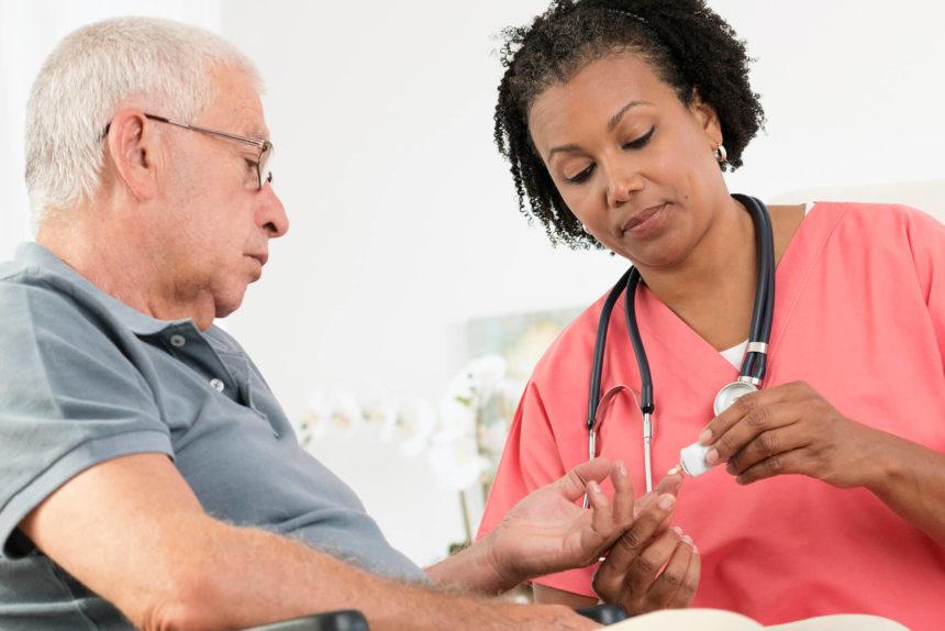 Nurse checks blood glucose of patient.