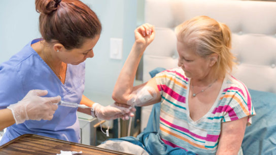 A nurse flushes out a patient's PICC line.