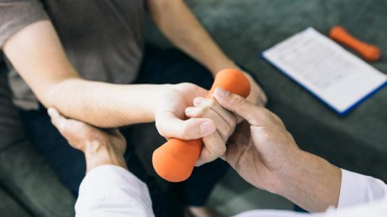 Testing a patient's upper limb strength.