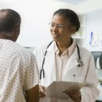 Black female doctor speaking to a Black male patient