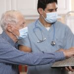 Doctor and patient wearing masks looking at laptop