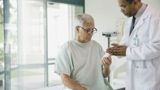 A doctor explains a medication to an older patient.