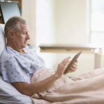 Patient reading on hospital bed.